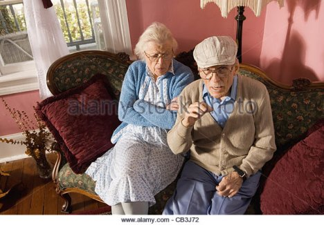 grumpy-senior-couple-sitting-on-sofa-in-living-room-cb3j72.jpg
